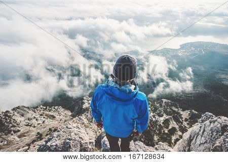 Man on mountain cliff enjoying aerial view over clouds alone Travel Lifestyle concept adventure active vacations outdoor freedom and happiness emotions