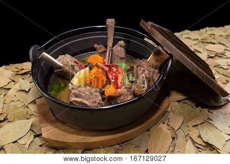 Beef short ribs with traditional chilli sauce carrot and potato in pot on leaf background