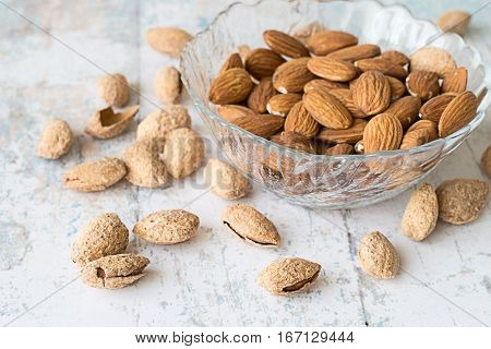 Almonds, peeled kernels in a glass vase and whole nuts on  old wooden table.