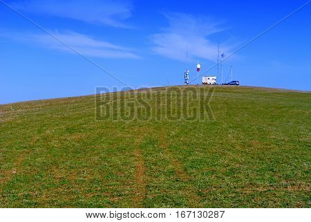 Transmitter on the hill green meadow and blue sky