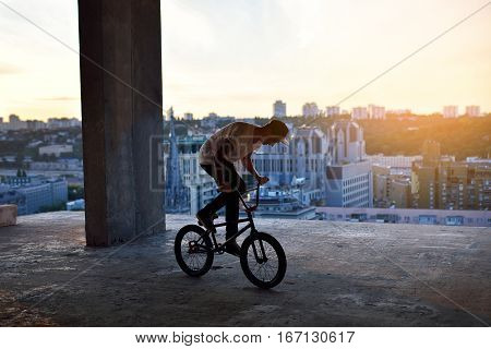 Silhouette Of A Man Jumping On Bmx Bike On Roof Of The House Against Sky At Sunset.