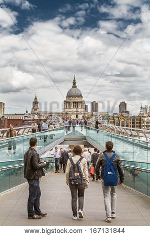 LONDON UK - JUNE 15 2016: Tourists stand on the Millenium Bridge looking at St Pauls Cathedral