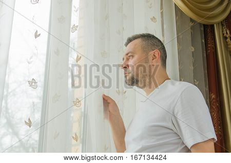 young man looking through a window blind and smiling