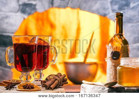 Mulled wine and honey. Opened bottle and pan on the background