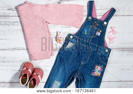Baby girl clothes collection - denim overalls, pink knitted sweater, leather boots, hair bows