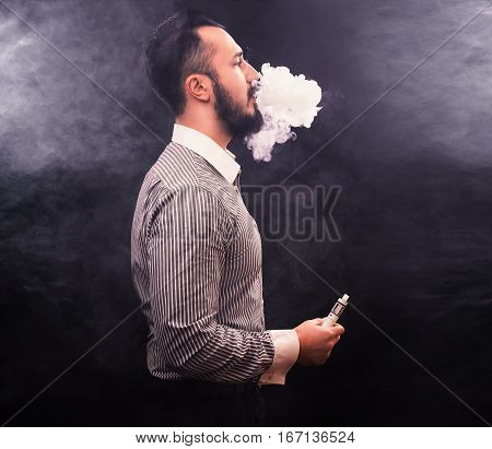 Men With Beard Vaping And Releases A Cloud Of Vapor.