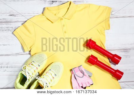 Sport clothes and equipment on wooden background - yellow polo shirt, yellow running shoes, pink gloves, red dumbbells