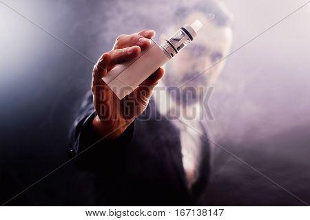 man's hand holding electronic vaporizer, vapor concept