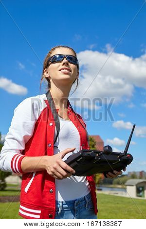 Woman with remote control and flying surveillance drone