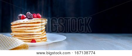 Pancake on a white plate with fruit and powdered sugar on a wooden background