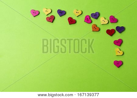 Heart shaped colorful wooden sewing buttons on greenery background. Copy space for text. Top view. Frame, background of button