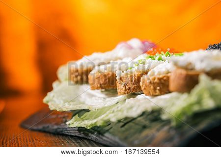 Toasts of wholemeal bread with cottage cheese spread and tops. Fire lighting background