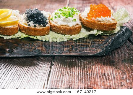 Natural farmer cheese sandwiches. Tops of roe, caviar, onions and lemon