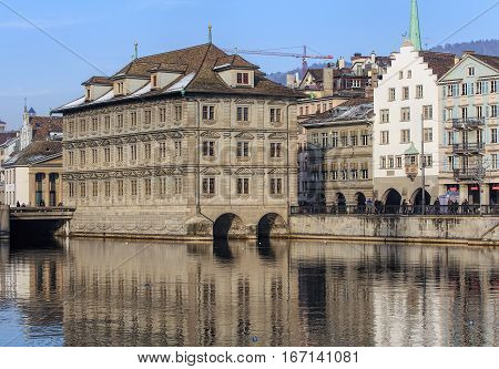 Zurich, Switzerland - 27 January, 2017: historical part of city and the Limmat river in wintertime. The leftmost building in the foreground is the Zurich Town Hall (German: Rathaus). Zurich is the largest city in Switzerland.