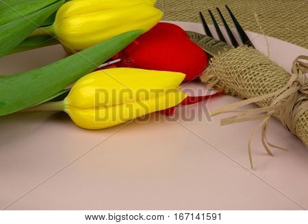 Cutlery wrapped in woven napkin on a brigh pink plate two tulips and red heart. Close horizontal view