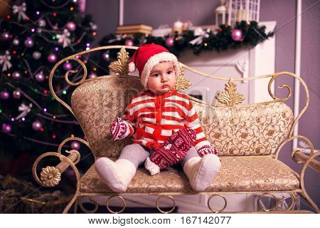Beautiful Little Baby Celebrates Christmas. New Year's Holidays. Baby In A Christmas Costume With Gi