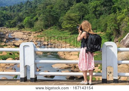 Cute young female wildlife photographer during safari making photos of landscape