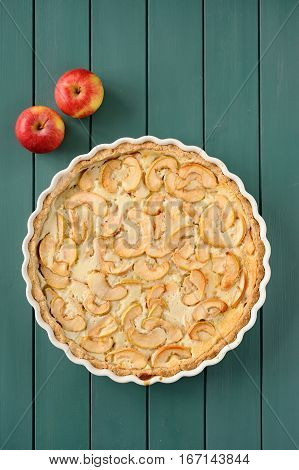 Apple tart with whole apples on turquoise stripped background vertical