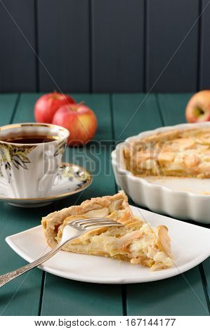 Apple tart with cup of tea and whole apples vertical