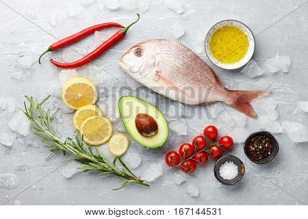 Fish cooking: fresh red Japanese seabream, lemon slices, avocado fruit, chili pepper, cherry tomatoes, olive oil, rosemary and spices on gray stone background