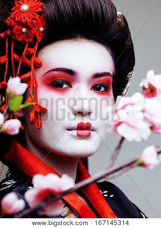 young pretty geisha in black kimono among sakura, asian ethno close up