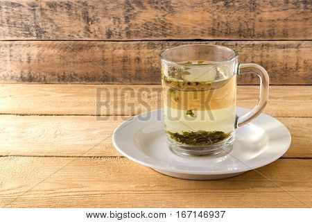 Green tea in a transparent mug on a wooden background