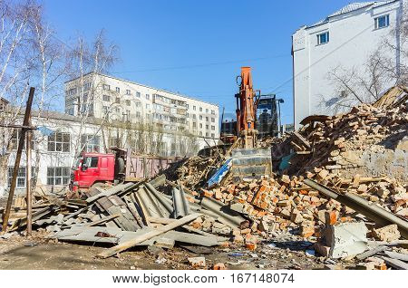 Tyumen, Russia - April 6, 2015: Destroyed two-storeyed barrack at address Holodilnaya street 88. Excavator works on loading of construction garbage from demolished house into truck