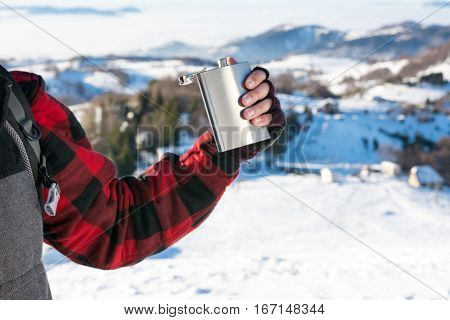 Male Hand Holding Hip Flask On A Snowy Mountain