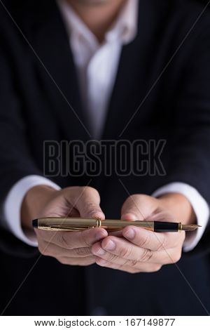 A man in black casual suit giving a gold fountain pen for sign the contract in formal way.