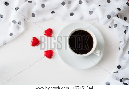 St Valentines day background - cup of coffee heart shaped candies with frame of chiffon polka dot scarf. St Valentines day  still life with blank card for St Valentines day  message