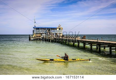 Anna Maria Island, FL, USA - December 20: Man in a yellow canoe paddles past the Rod & Reel Pier on Anna Maria Island Florida