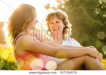 Mother and her teenage daughter sitting on grass and talking with setting sun in background