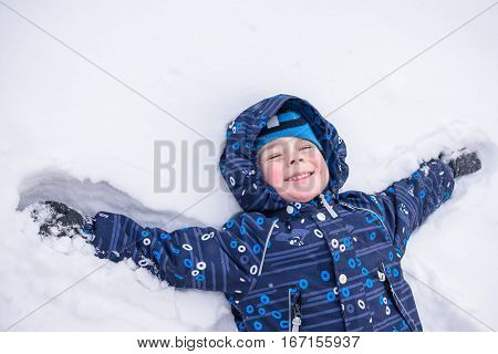 Cute Little Kid Boy In Colorful Winter Clothes Making Snow Angel, Laying Down On . Active Outdoors L