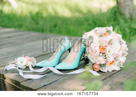 Beautiful Wedding bridal pink and violet Bouquet with high heels mint shoes on wooden background. Floristic composition, bradal set
