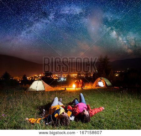Hikers Enjoying The Bright Stars And Lying On The Grass