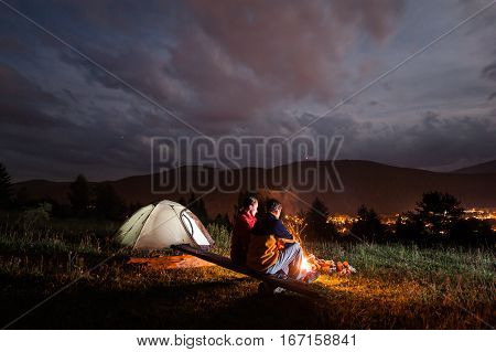 Romantic Couple Sitting By Bonfire Under Cloudy Sky