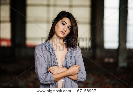 Close Up Portrait Of Young Cute Brunette Girl With Slightly Bust Posed On Abandoned Place.