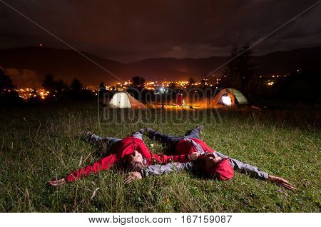 Tourist Couple Admiring The Night Sky And Lying On The Grass
