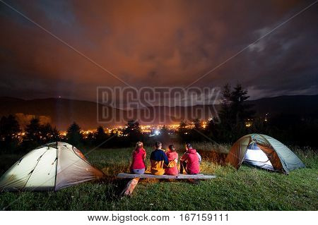 Friends Watching Fire Together Beside Camp And Tents