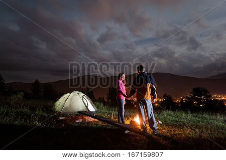 Pair Holding Hands, Standing Near Camp, Looking At Each Other