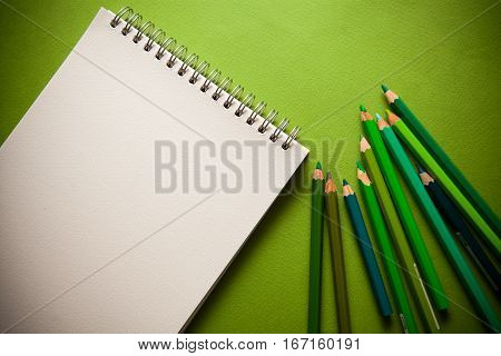 green shades pensils on green paper background