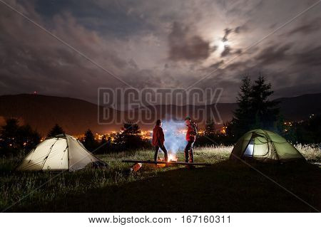 Girl And Guy Stands Near Camp, Looks On The Campfire