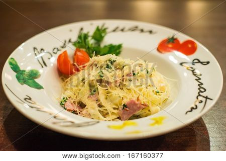 Pasta Carbonara with bacon and grated cheese adorned with cherry tomatoes