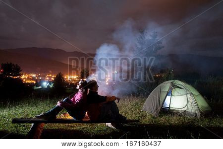 Two Campers Sitting Back To Back Near Tent And Campfire