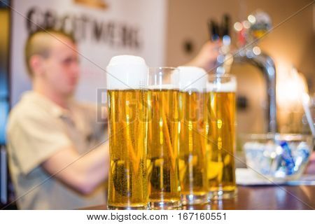 Bartender pours the foamy beer in glasses with bubbles