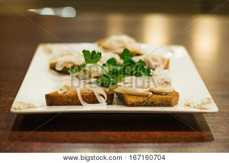Toasts with herring and onion decorated with parsley