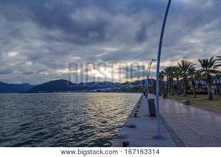 Marmaris street on port during sunset among clouds.