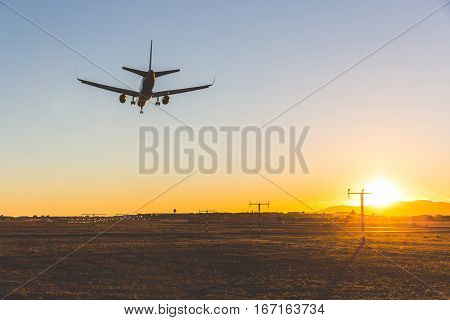 Airplane landing at sunset bottom view. Backlight view of a commercial aircraft on final approach in Mallorca. Wide angle image travel and wanderlust concepts.
