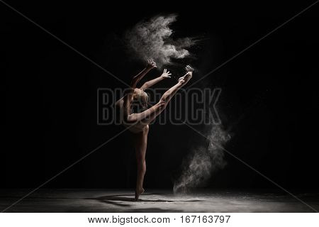 Graceful woman dancing in cloud of white dust studio shot