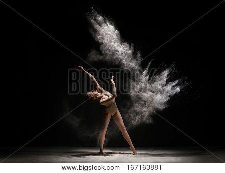 Slender woman dancing in cloud of white dust studio shot